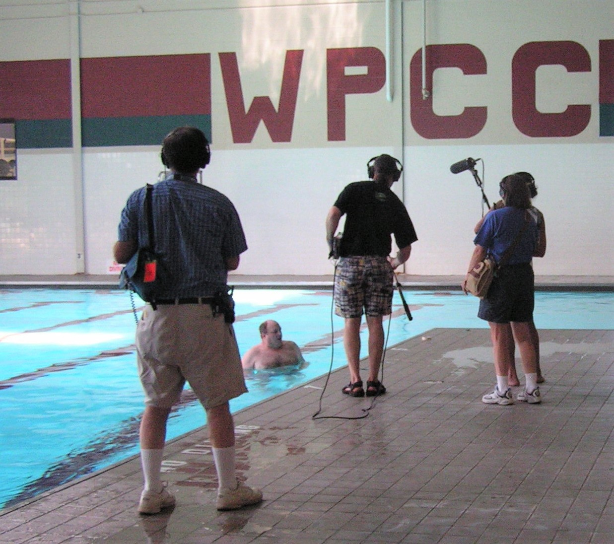 Two men and two women at a swimming pool recording the water sounds